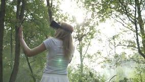 Mujer joven que lleva las auriculares de VR en el bosque que experimenta realidad virtual aumentada - almacen de metraje de vídeo