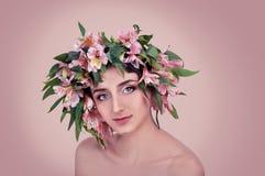 Mujer joven que lleva las flores rosadas en su cabeza Fotos de archivo libres de regalías