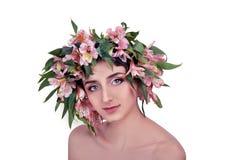 Mujer joven que lleva las flores rosadas en su cabeza Imagen de archivo