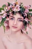 Mujer joven que lleva las flores rosadas en su cabeza Imagen de archivo libre de regalías