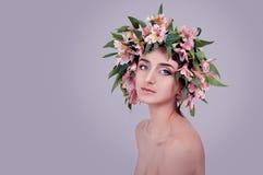 Mujer joven que lleva las flores rosadas en su cabeza Imágenes de archivo libres de regalías