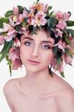 Mujer joven que lleva las flores rosadas en su cabeza Fotografía de archivo