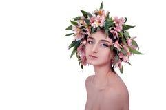Mujer joven que lleva las flores rosadas en su cabeza Fotografía de archivo libre de regalías