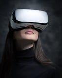 Mujer joven que lleva los vidrios de la realidad virtual Fotografía de archivo