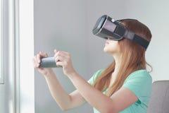 Mujer joven que lleva los vidrios de la realidad virtual en casa imágenes de archivo libres de regalías