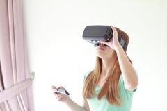 Mujer joven que lleva los vidrios de la realidad virtual en casa fotografía de archivo libre de regalías