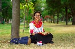 Mujer joven que lleva los vidrios tradicionales, la falda andina y la blusa con el collar rojo a juego, sentándose en hierba al l Imágenes de archivo libres de regalías