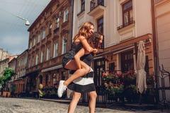 Mujer joven que lleva a su mejor amigo en ella detrás en la calle de la ciudad Muchachas adolescentes felices que ríen y que se d Imagenes de archivo