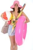 Mujer joven que lleva un bañador el día de fiesta que lleva una pelota de playa Foto de archivo libre de regalías