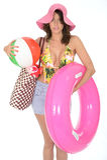 Mujer joven que lleva un bañador el día de fiesta que lleva una pelota de playa Fotografía de archivo libre de regalías