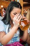 Mujer joven que lleva un dirndl con la taza de cerveza Imagen de archivo libre de regalías