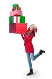 Mujer joven que lleva una pila de presentes Fotos de archivo libres de regalías