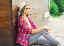 Mujer joven que lleva una reclinación que se sienta rosada de la camisa y del sombrero del verano Fotos de archivo