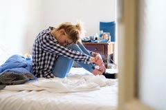 Mujer joven que llora en cama después de violencia en el hogar en casa Fotos de archivo