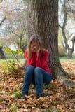 Mujer joven que llora en el parque del otoño Foto de archivo