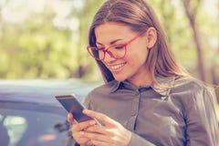 Mujer joven que manda un SMS en el teléfono elegante al aire libre en un día del otoño Fotografía de archivo