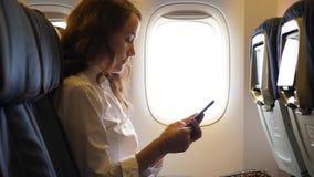Mujer joven que manda un SMS en smartphone en avión de pasajeros almacen de metraje de vídeo