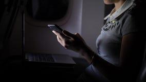Mujer joven que manda un SMS en smartphone en avión de pasajeros en la noche almacen de metraje de vídeo