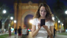 Mujer joven que manda un SMS en smartphone contra Arc de Triomf, Barcelona almacen de metraje de vídeo