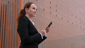 Mujer joven que manda un SMS en smartphone en el centro de la ciudad de la ciudad almacen de metraje de vídeo