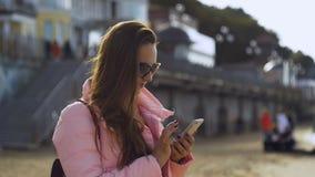Mujer joven que manda un SMS en smartphone en el mar almacen de video