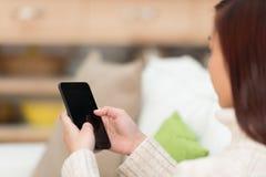 Mujer joven que manda un SMS en su smartphone Foto de archivo