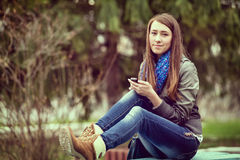 Mujer joven que manda un SMS en su teléfono móvil Fotos de archivo