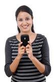 Mujer joven que manda un SMS en su teléfono móvil Foto de archivo