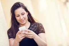 Mujer joven que manda un SMS en su teléfono móvil Fotografía de archivo