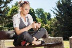 Mujer joven que manda un SMS en un teléfono celular Imágenes de archivo libres de regalías