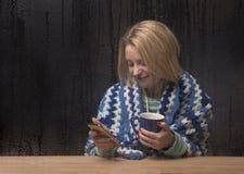 Mujer joven que manda un SMS en un teléfono en un día lluvioso imagen de archivo libre de regalías