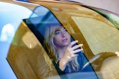 Mujer joven que manda un SMS mientras que conduce el coche Fotos de archivo libres de regalías