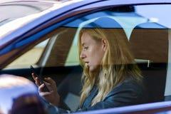Mujer joven que manda un SMS mientras que conduce el coche Foto de archivo