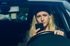Mujer joven que manda un SMS mientras que conduce el coche Fotos de archivo