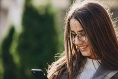 Mujer joven que manda un SMS o que usa a smartphone foto de archivo