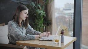 Mujer joven que mecanografía en el teclado, charla, bloging Trabajo del Freelancer sobre netbook en coworking moderno Gente acert metrajes