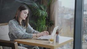 Mujer joven que mecanografía en el teclado, charla, bloging Trabajo del Freelancer sobre netbook en coworking moderno Gente acert almacen de metraje de vídeo
