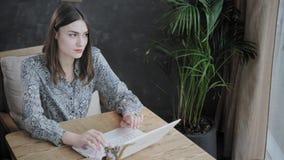 Mujer joven que mecanografía en el teclado, charla, bloging Trabajo del Freelancer sobre netbook en coworking moderno Gente acert almacen de video