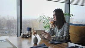 Mujer joven que mecanografía en la tableta, charla, bloging Trabajo del Freelancer en coworking moderno del caf? Gente acertada metrajes