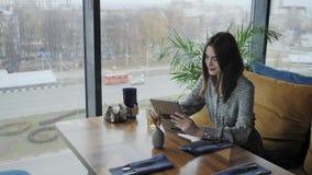 Mujer joven que mecanografía en la tableta, charla, bloging Trabajo del Freelancer en coworking moderno del caf? Gente acertada almacen de video