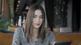 Mujer joven que mecanografía en la tableta, charla, bloging Trabajo del Freelancer en coworking moderno del caf? Gente acertada almacen de metraje de vídeo