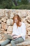 Mujer joven que mecanografía en su teclado del ordenador portátil Foto de archivo libre de regalías