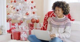 Mujer joven que mecanografía en un ordenador portátil en la Navidad Foto de archivo