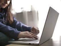 Mujer joven que mecanografía en un ordenador portátil mientras que se sienta en casa en un sofá imagenes de archivo