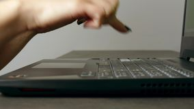 Mujer joven que mecanografía muy lento en el teclado del ordenador portátil almacen de metraje de vídeo