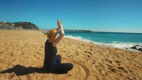 Mujer joven que medita en actitud del loto en la playa del mar Yoga practicante de la muchacha deportiva almacen de metraje de vídeo