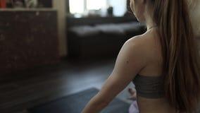Mujer joven que medita en clase de la yoga almacen de metraje de vídeo