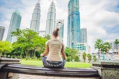 Mujer joven que medita en el parque en el fondo de rascacielos Foto de archivo libre de regalías