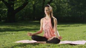 Mujer joven que medita en parque soleado almacen de video