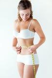 Mujer joven que mide su cintura por la cinta de la medida Imágenes de archivo libres de regalías